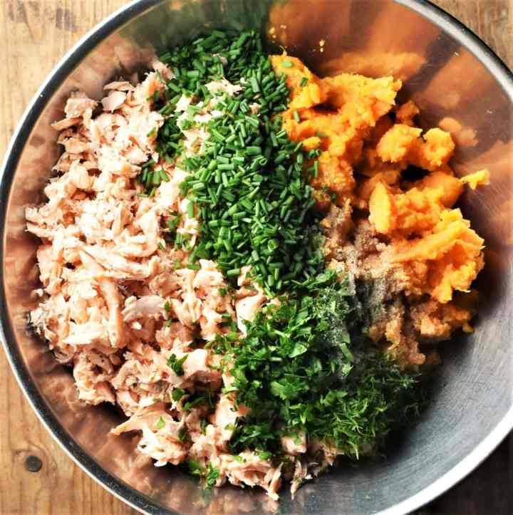 Flaked salmon, mashed sweet potato and chopped herbs in large metal bowl.