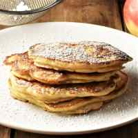 Side view of apple pancakes dusted with icing sugar stacked on plate.