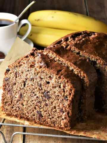 Side view of banana date bread with coffee cup and bananas in background.
