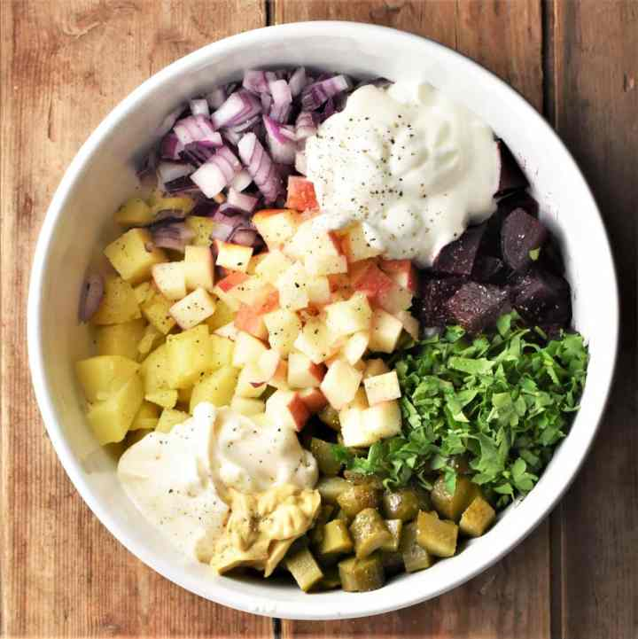 Chopped vegetables, herbs and yogurt in mixing bowl.