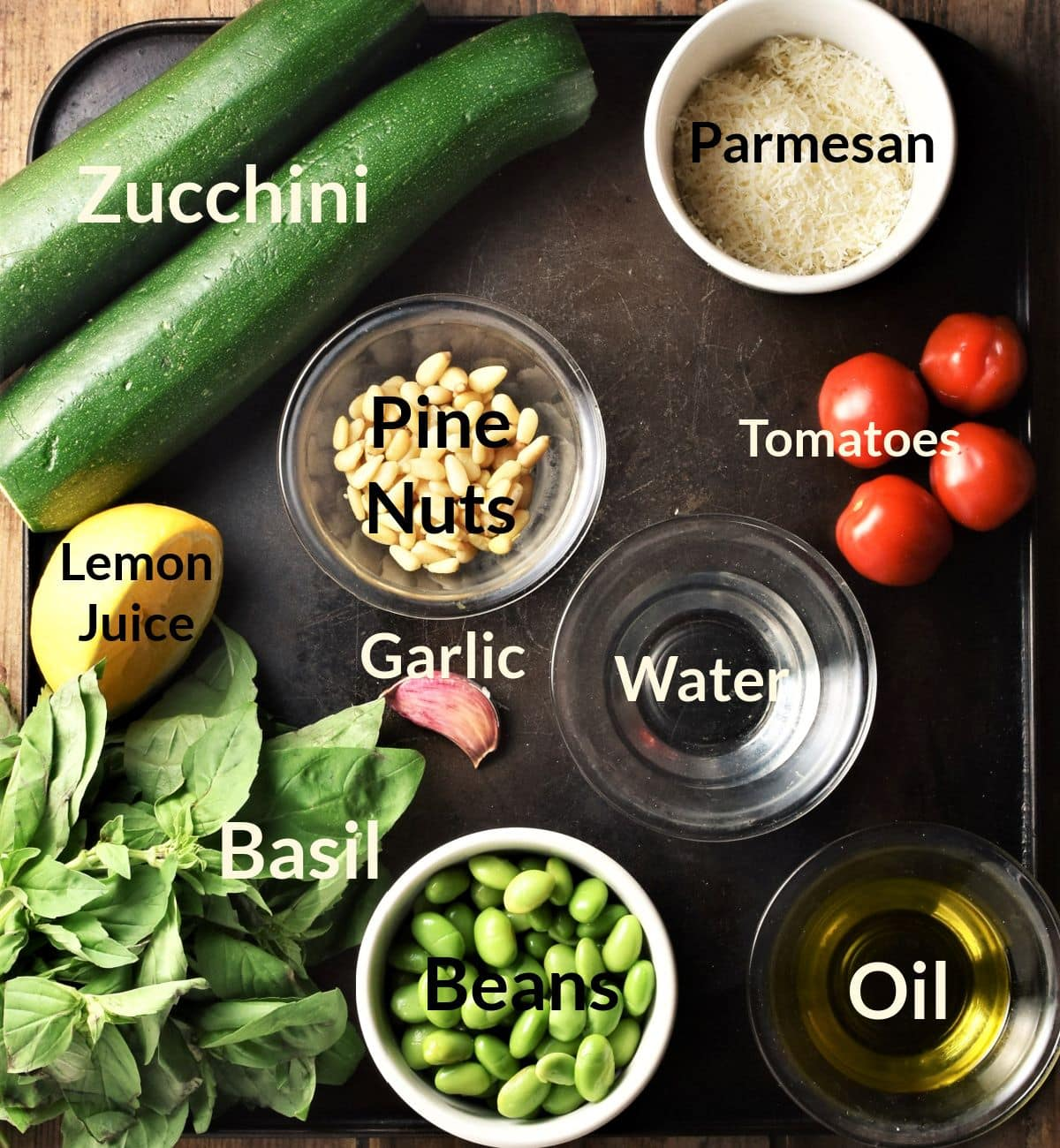 Ingredients for making pesto zoodles salad in individual dishes.