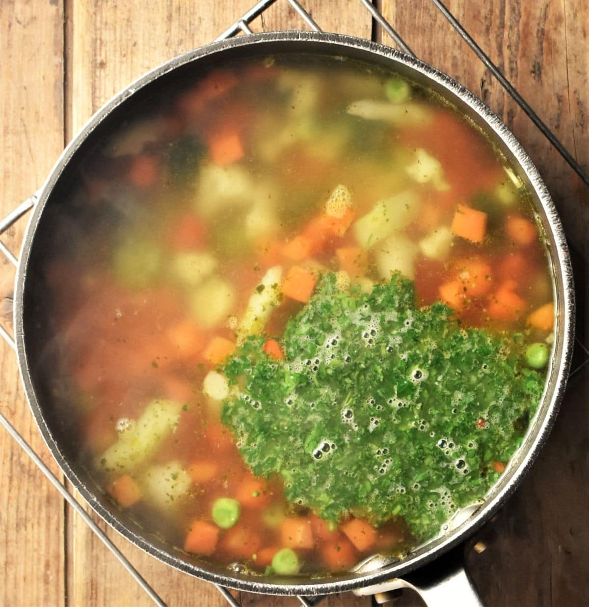 Making chunky vegetable soup in pot with fresh herbs.