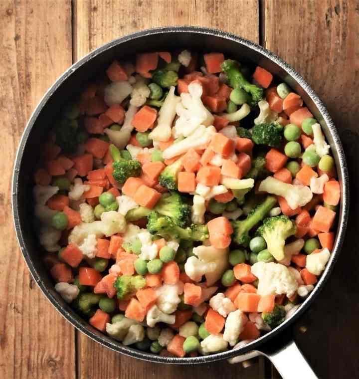 Frozen vegetables inside soup pot.