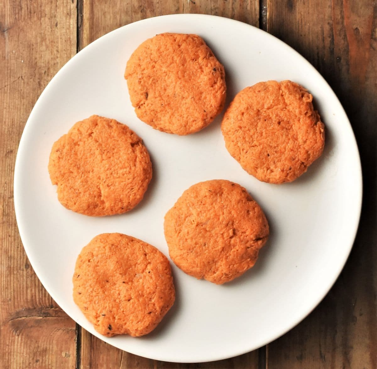 5 uncooked sweet potato cakes on top of white plate.