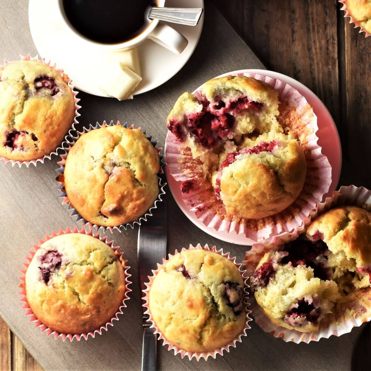 Top down view of raspberry white chocolate muffins in red liners and coffee in white cup.