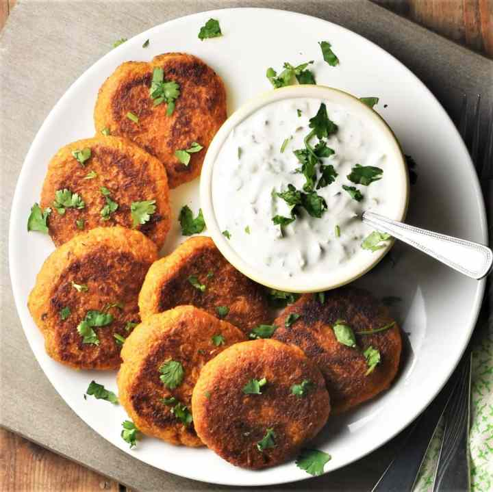 Top down view of sweet potato fritters on white plate with yogurt dip.