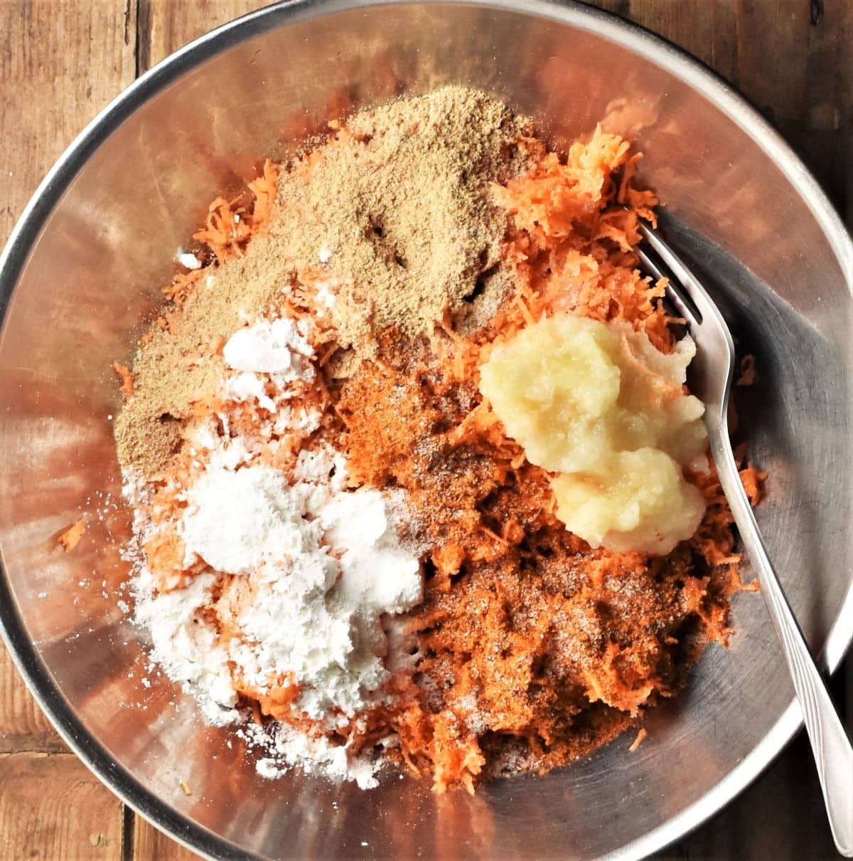 Finely grated sweet potato with spices for making fritters in metal bowl.