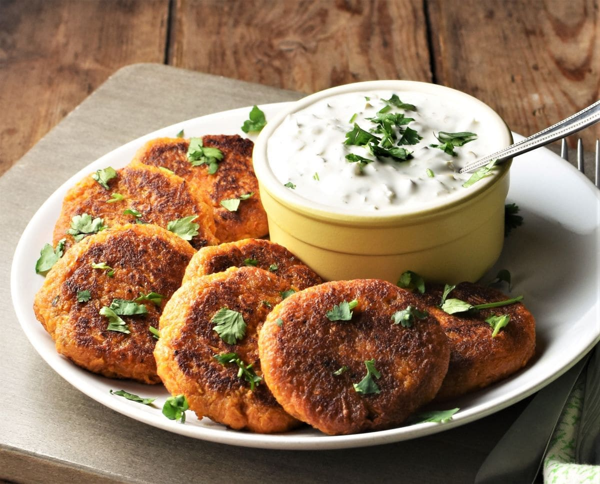 Side view of sweet potato fritters with herbs and yogurt dip.