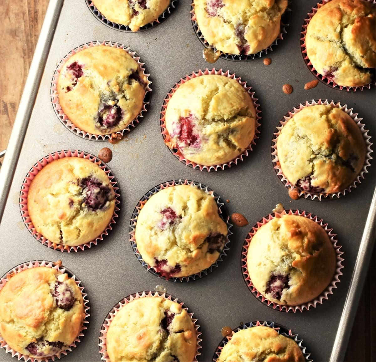 Top down view of 12 raspberry muffins inside muffin tin.