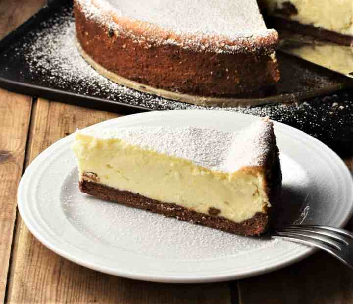 Side view of Polish sernik cheesecake on top of plate with cheesecake in background.
