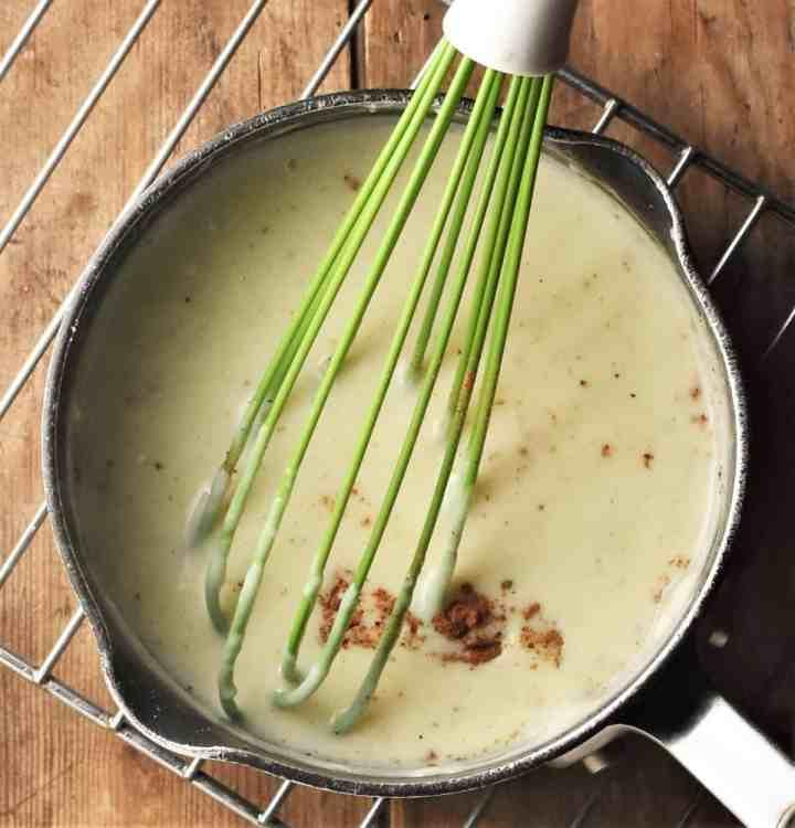 Whisking bechamel sauce in small pan.
