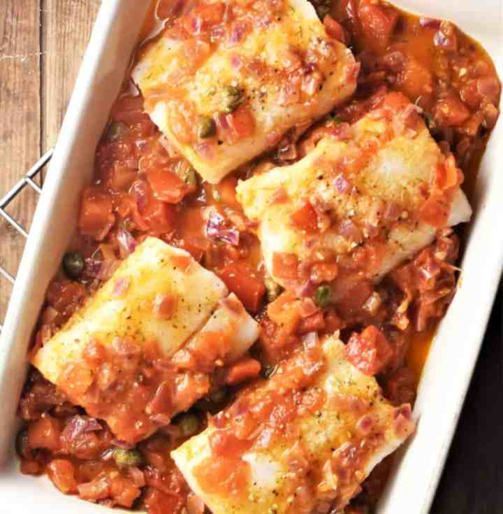 Top down view of 4 cod pieces in chunky tomato sauce in rectangular dish.