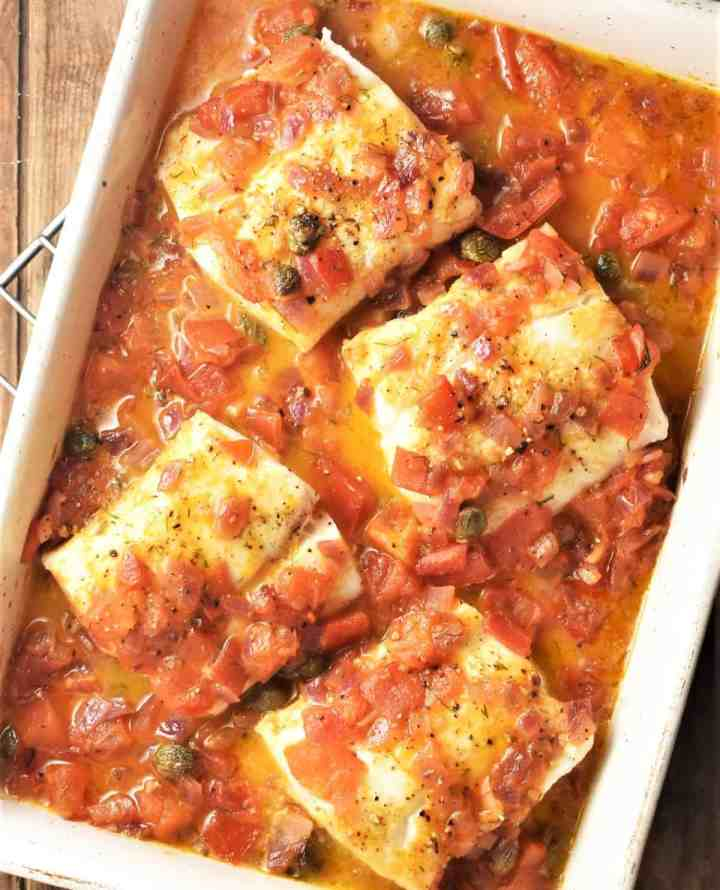 Baked cod in chunky tomato sauce in casserole dish.