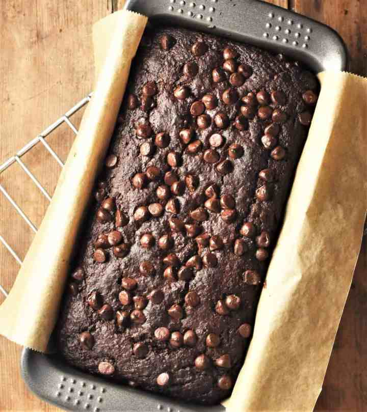 Top down view of chocolate cake in loaf pan with parchment.