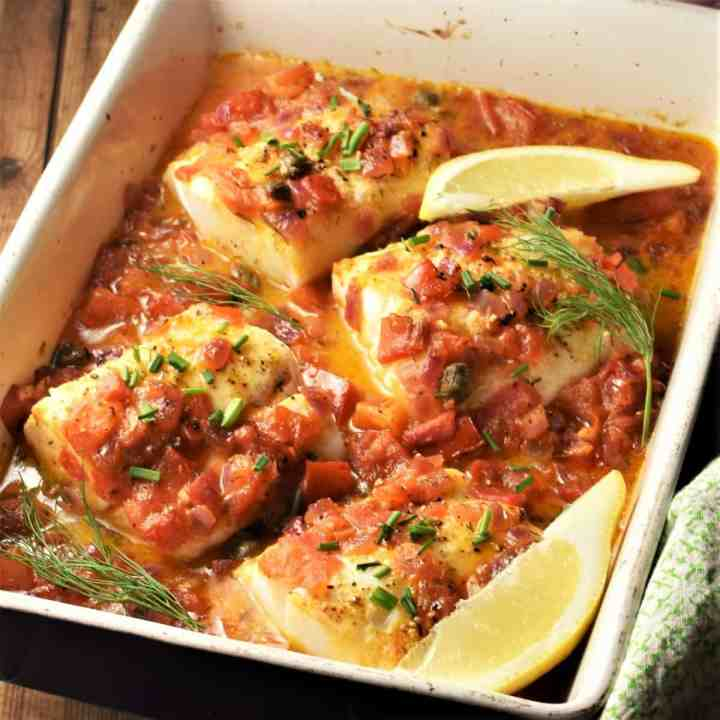 Side view of 4 cod pieces in tomato sauce in casserole dish with lemon wedges.