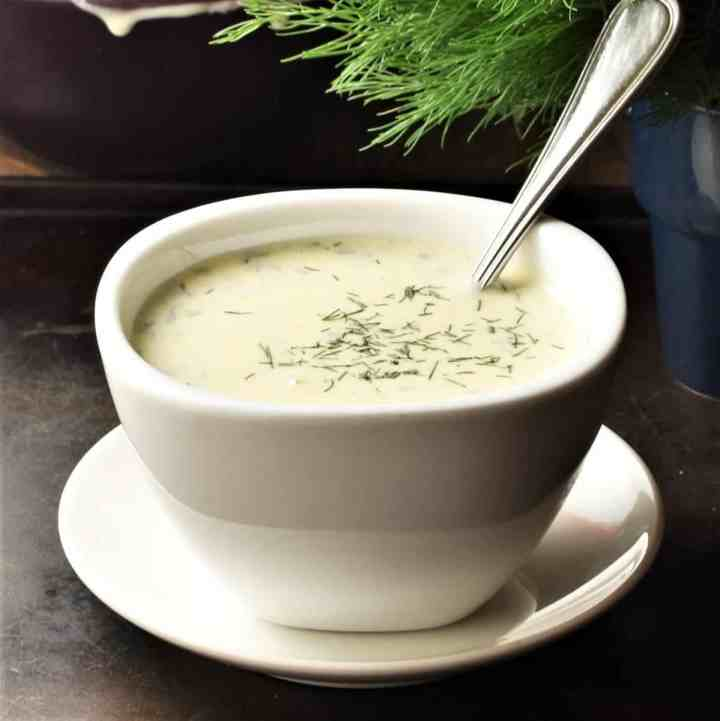 Side view of creamy dill mustard sauce in white bowl with spoon on saucer.