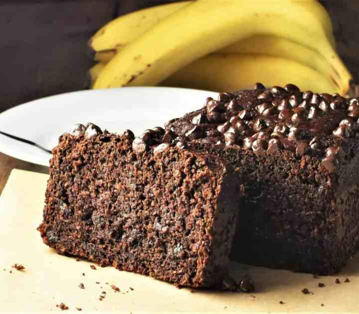 Side view of chocolate loaf cake with plate and bananas in background.