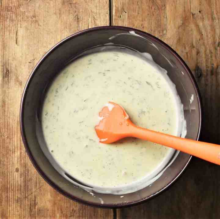 Top down view of creamy dill sauce in purple bowl with orange spatula.