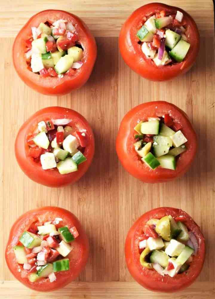 Top down view of 6 salad stuffed tomatoes on top of board.