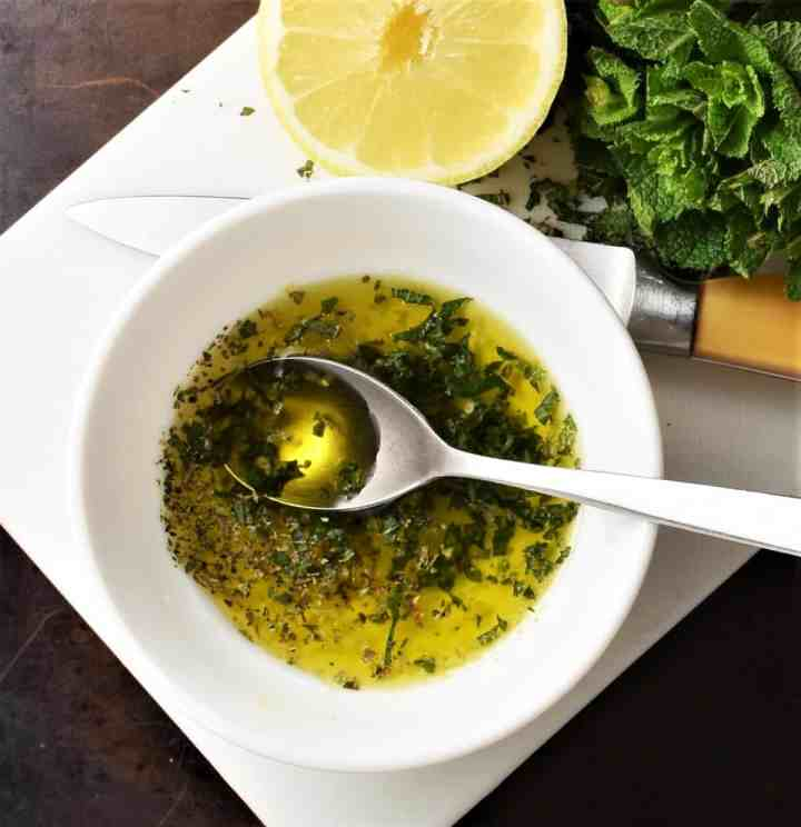 Salad dressing in white bowl with spoon, lemon and herbs.