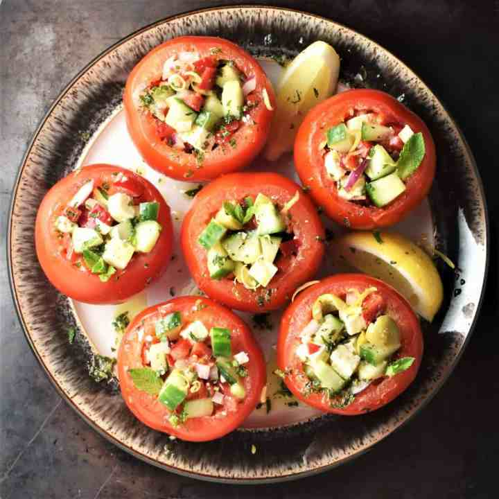 Top down view of vegetarian stuffed tomatoes with lemon wedges on brown plate.