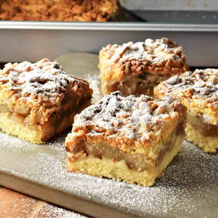 Side view of Polish apple cake slices on top of grey board.