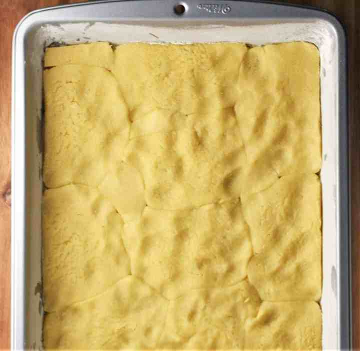 Assembling szarlotka recipe in rectangular pan.