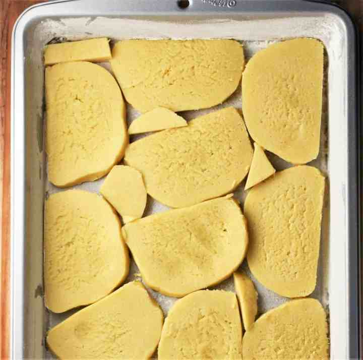 Slices of dough at the bottom of rectangular pan.