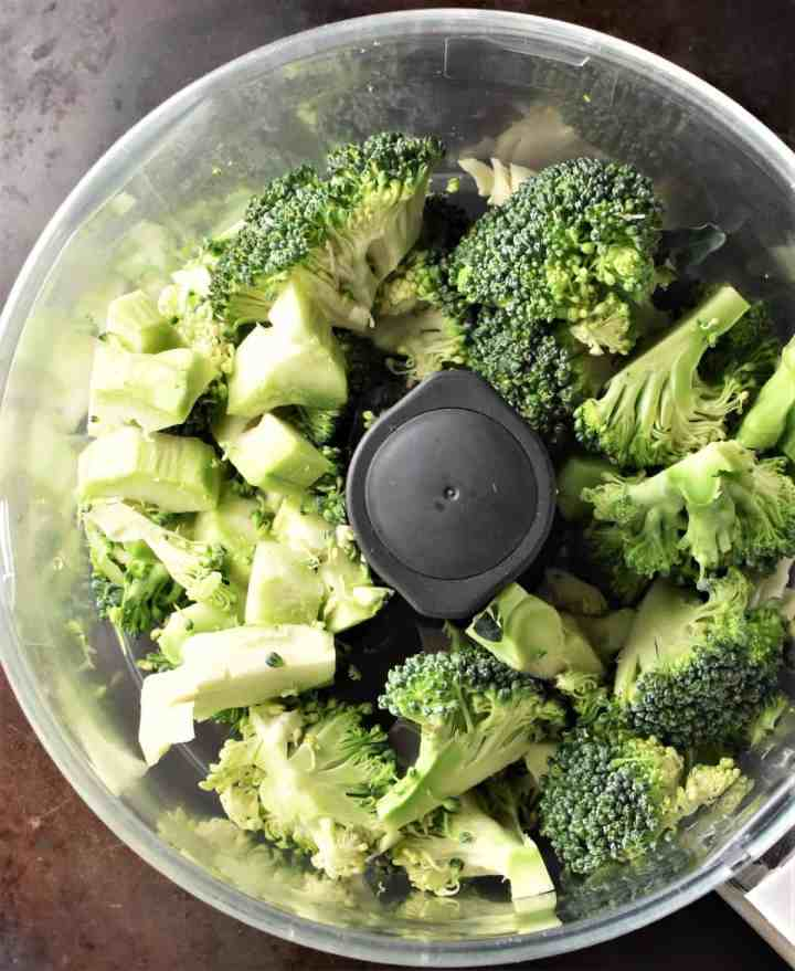 Chunks of raw broccoli in blender bowl.