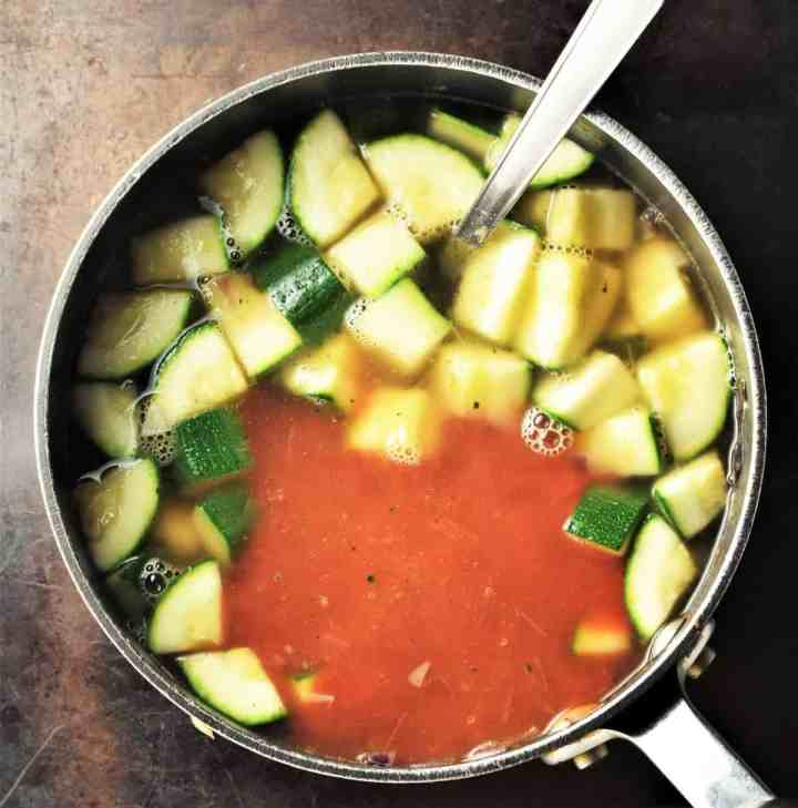 Cubed zucchini and tomato puree in pot with spoon.