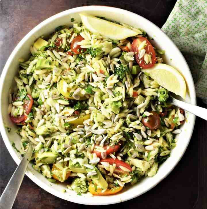 Broccoli and pasta salad with lemon wedges in white bowl with spoons.