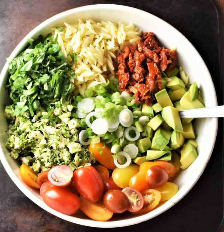 Broccoli and pasta salad ingredients assembled in large white bowl.