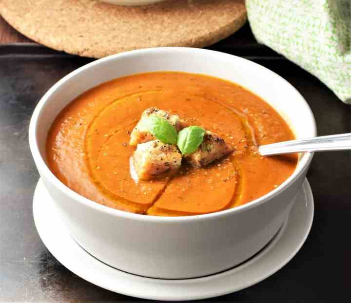 Side view of creamy tomato soup with croutons and spoon in white bowl.