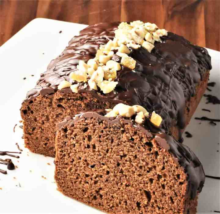 Side view of gingerbread loaf cake with chocolate drizzle and crushed nuts on top.