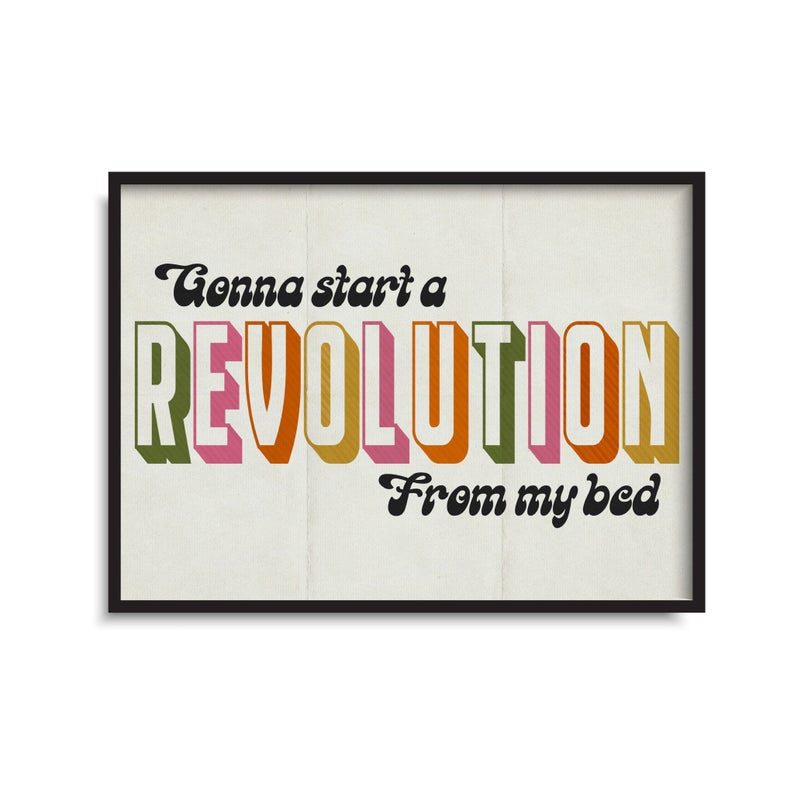 Posterwith a white background in a black frame. Gonna start a revolution from my bed is written on the poster. Gonna start a and from my bed are written in black scrol font and revolution is written in multicoloured chunky letters