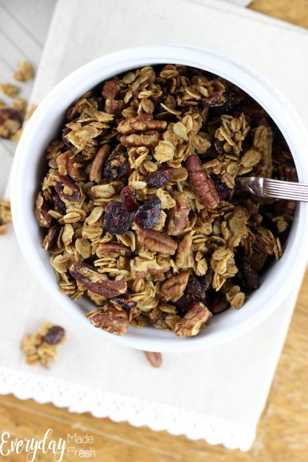Looking down on to a bowl of gingerbread granola. Clusters of oats, cranberries and pecans.