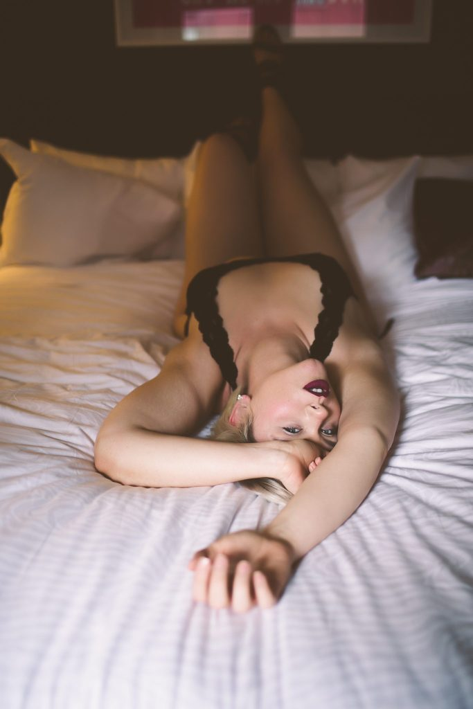 Woman laying on bed for an intimate photograph