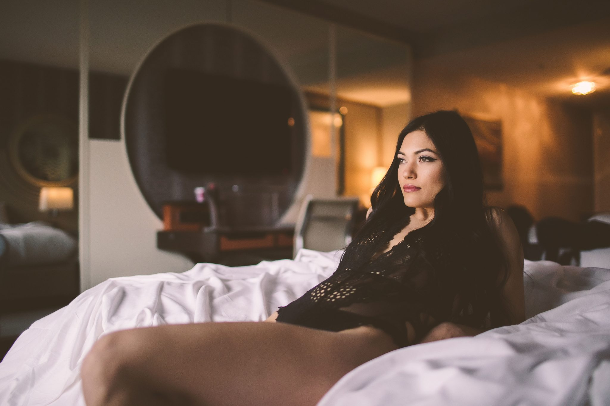 A model leaning back on a bed during a photo session