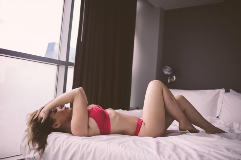 A boudoir model wearing sexy red lingerie
