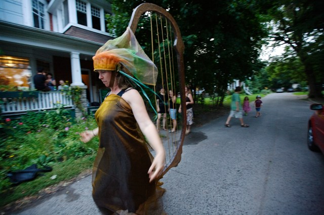 image of Leigh Macdonald wearing a flowing deep golden brown tunic with a giant harp emerging from her head and trailing town behind her to her sandaled feet