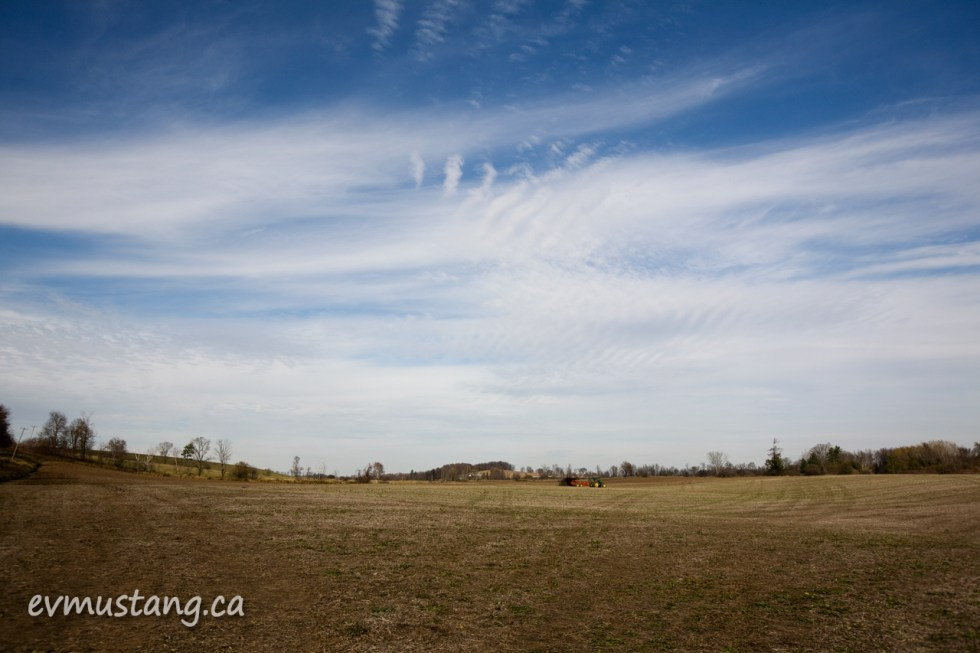 image of autumn field with spreader in distance