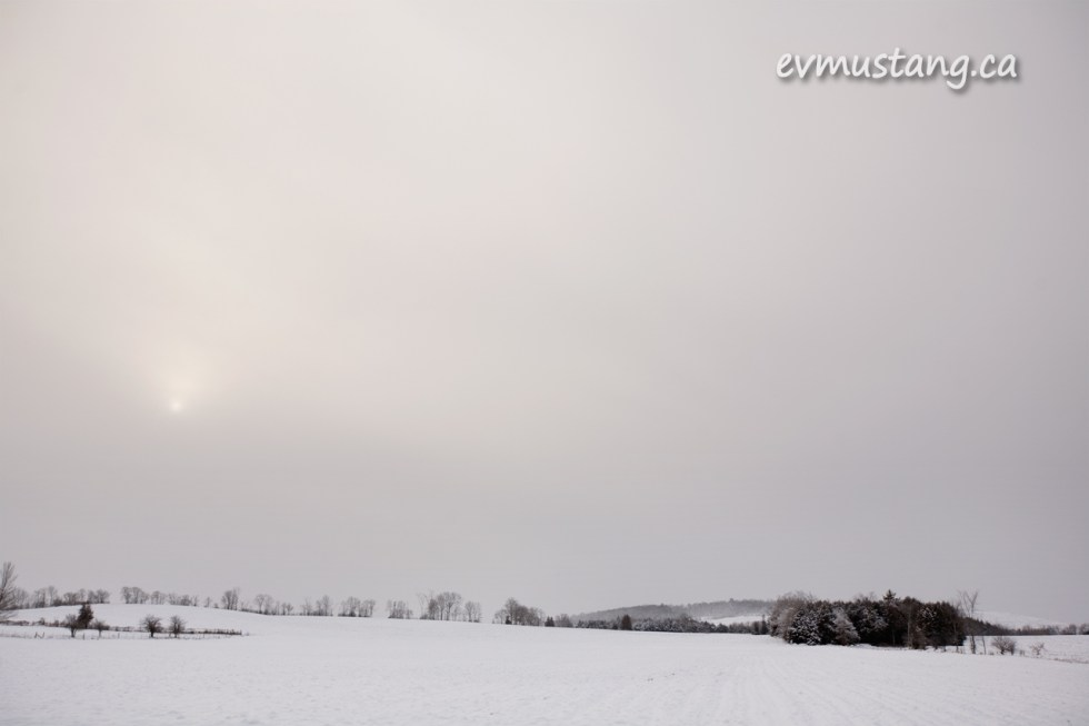 image of a snowy field with the sun smudged behind cloud
