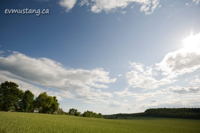 image of spring clouds over sunny field
