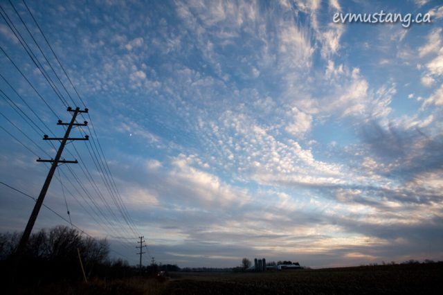 image of field at sunset with clouds, moon and telephone pole