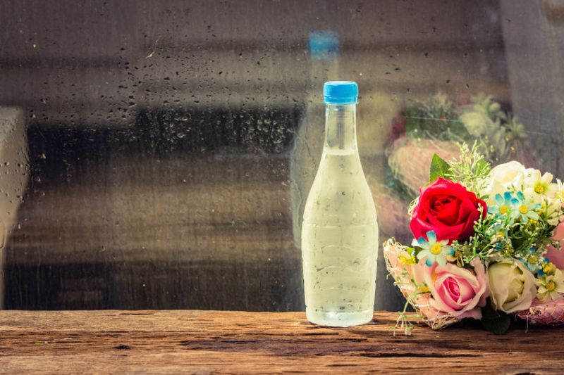 31879659 – cold water in bottle with flowers on wood table.beside glass window