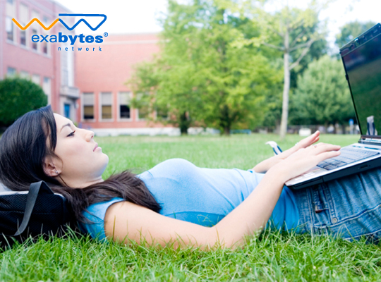 a female student laying on grass and look at laptop