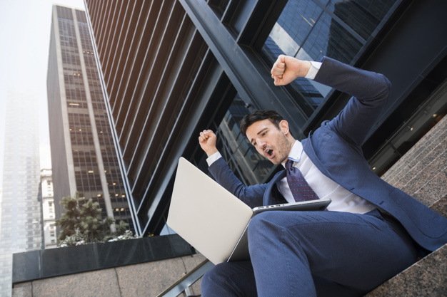 businessman-with-laptop-celebrating-success_23-2147932214