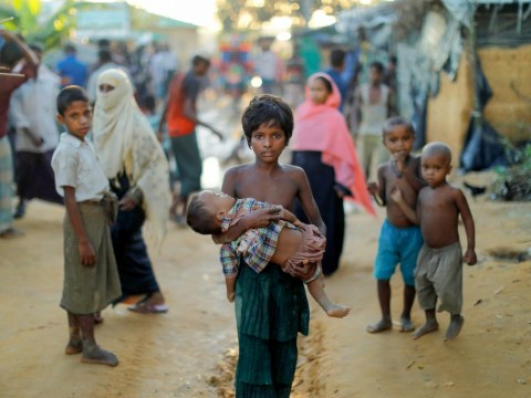 A young Rohingya refugee carries a child while walking at a camp near Cox's Bazar, Bangladesh. Photo: CNS photo/Reuters