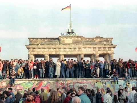People stand atop a section of the Berlin Wall in front of the Brandenburg Gate on 10 November 1989. File photo: CNS/Reuters