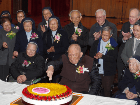 Father Chao, flanked by Sister Bernadette Hu (right) and Sister Magdalena Lui (left), surrounded by their fellow jubilarians, cuts the cake, during the tea reception at Caritas Hall on December 7.